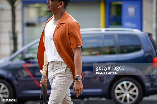 A guest wears an orange shirt a white tshirt a watch outside the Y/Project show during Paris Fashion Week Menswear Spring/Summer 2018 on June 21 2017...