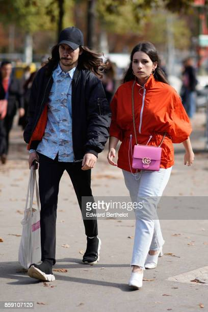 A guest wears an orange top white cropped pants a pink Gucci bag white shoes outside Issey Miyake during Paris Fashion Week Womenswear Spring/Summer...