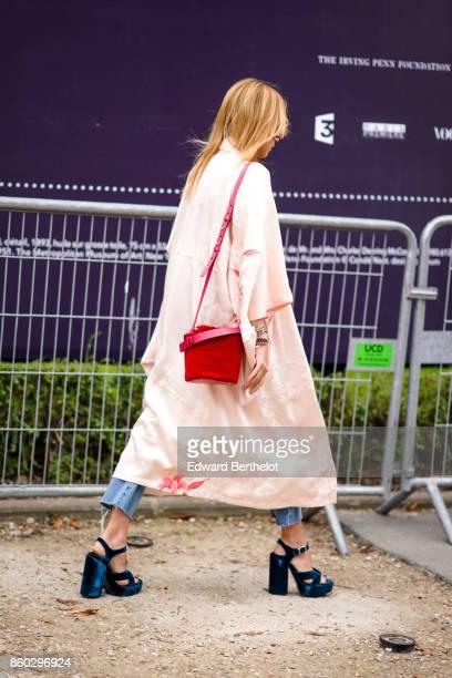A guest wears an oversize pale pink light coat a red bag ripped blue jeans blue velvet platform shoes outside Lanvin during Paris Fashion Week...