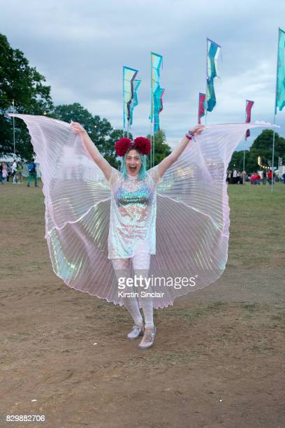 A guest wears angel wings a Sequin dress and jelly sandals on day 3 of Wilderness Festival on August 5 2017 in Cornbury Park Oxford England