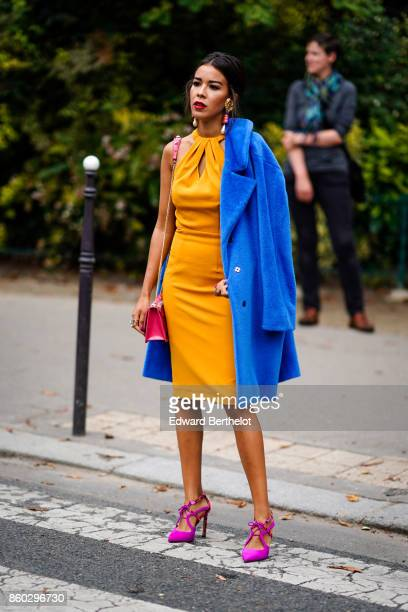 A guest wears big earrings a royal blue coat an ochre yellow raglan dress a pink bag pink shoes outside Lanvin during Paris Fashion Week Womenswear...