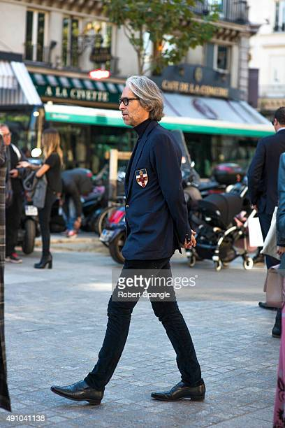 Guest wears blue blazer with school crest turtleneck and black loafers after Isabel Marant at Palais Royal during Paris Fashion Week Spring/Summer...