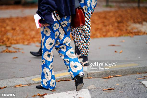 A guest wears blue pants with white floral prints outside Lanvin during Paris Fashion Week Womenswear Spring/Summer 2018 on September 27 2017 in...