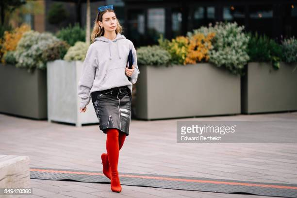 A guest wears blue sunglasses a gray hoodie top a skirt red thigh high boots outside Versus during London Fashion Week September 2017 on September 17...