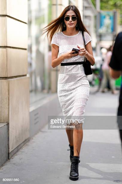 A guest wears circular sunglasses a white lace dress outside the Elie Saab show during Paris Fashion Week Haute Couture Fall/Winter 20172018 on July...