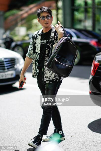 A guest wears converse shoes a shirt a black tshirt black pants outside the Y3 show during Paris Fashion Week Menswear Spring/Summer 2018 on June 25...