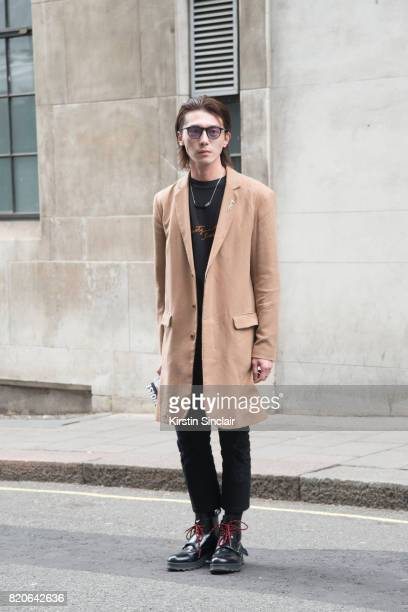 A guest wears Doc Martens boots and a camel jacket on day 1 of London Collections Men on June 9 2017 in Paris France