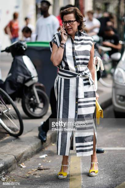 A guest wears glasses a black and white striped dress a yellow bag yellow heels outside the Y/Project show during Paris Fashion Week Menswear...