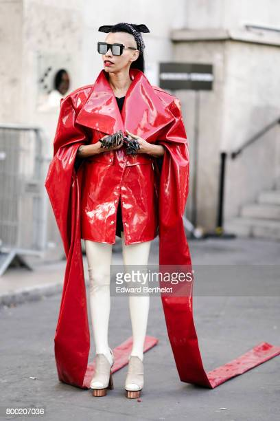A guest wears glasses a red vinyl kimono jacket with long sleeves white plastic leggings and gray shoes outside the 22/4 Hommes show during Paris...