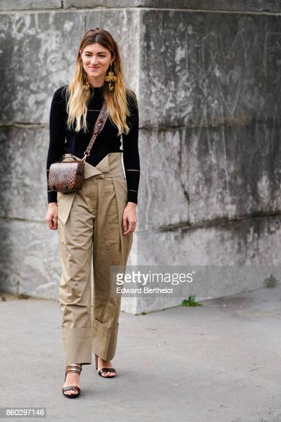 A guest wears huge earrings a black top a highwaisted camel pants with turnedup hems a brown reptile skin bag brown sandals outside Margiela during...