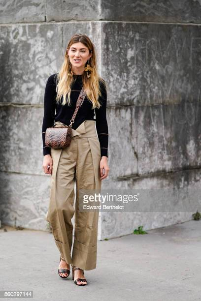 A guest wears huge earrings a black top highwaisted camel pants with turned up hems a brown reptile skin bag brown sandals outside Margiela during...