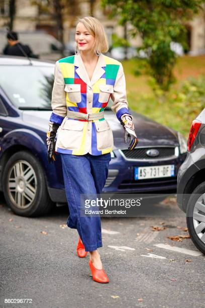 A guest wears huge hoop earrings a beige safari jacket with green yellow red and blue empiecements baggy blue jeans black gloves with multicolor...