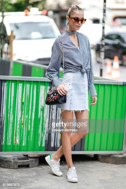 A guest wears leopard print sunglasses a checkered shirt a white denim ripped skirt Adidas green and white sneakers shoes a black leather bag with...