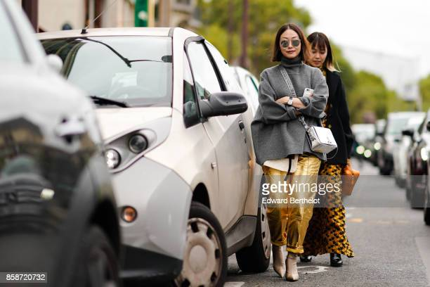 A guest wears mirror sior sunglasses a gray pull over golden pants an OffWhite silver bag outside Giambattista Valli during Paris Fashion Week...