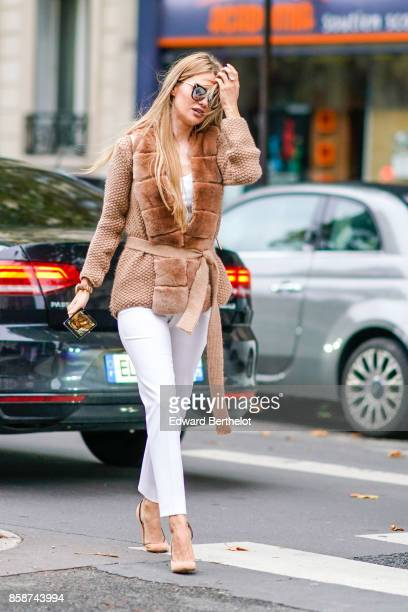 A guest wears mirror sunglasses a brown fluffy coat white pants outside Valentino during Paris Fashion Week Womenswear Spring/Summer 2018 on October...