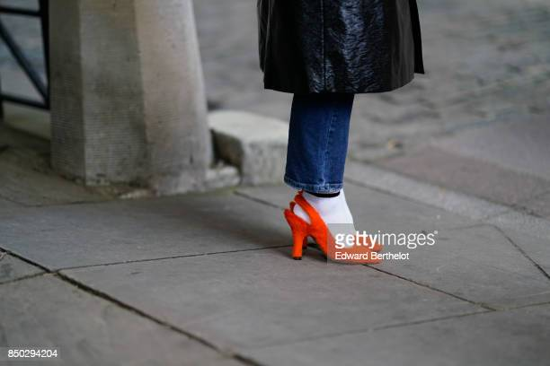 A guest wears orange shoes white socks a black leather trench coat jeans outside Simone Rocha during London Fashion Week September 2017 on September...