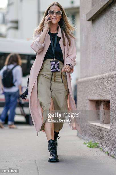 A guest wears pink sunglasses a pink jacket cropped camel pants a black top black shoes outside the Kenzo show during Paris Fashion Week Menswear...
