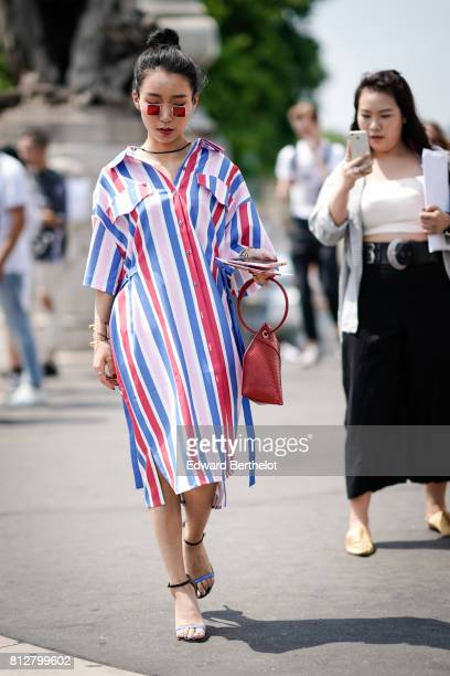 A guest wears red sunglasses a striped dress a red bag heels strap shoes outside the Icosae show during Paris Fashion Week Menswear Spring/Summer...