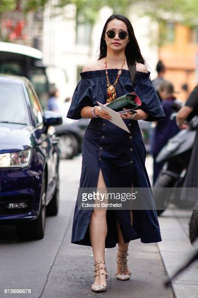 A guest wears round sunglasses an offshoulder blue dress Valentino Rockstud heels shoes a green bag outside the Elie Saab show during Paris Fashion...