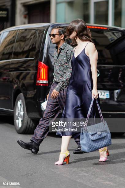 A guest wears silk dress pink heels and a blue Chanel bag outside the Thom Browne show during Paris Fashion Week Menswear Spring/Summer 2018 on June...