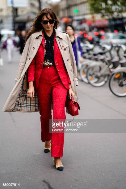 A guest wears sunglasses a beige trenchcoat a black scarf a moire effect red pantsuit beige and black shoes a red bag outside the Dries Van Noten...