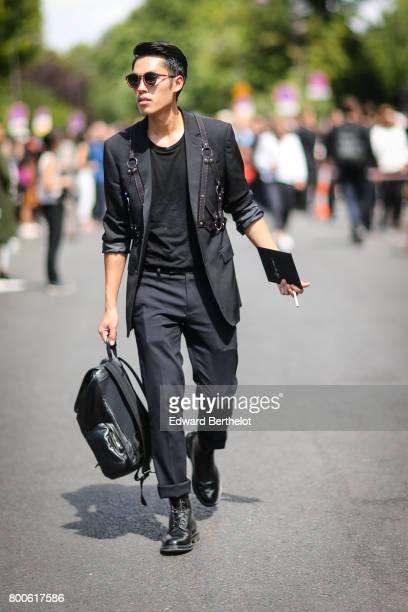 A guest wears sunglasses a black blazer jacket a black top black pants black shoes and a black backpack outside the Dior show during Paris Fashion...