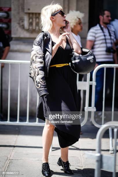 A guest wears sunglasses a black dress a yellow belt black shoes a bomber jacket outside the Jean Paul Gaultier show during Paris Fashion Week Haute...