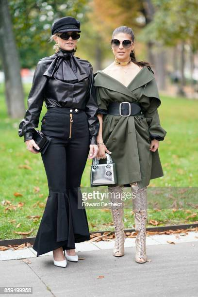 A guest wears sunglasses a black hat a black leather pusssy bow shirt black gored flare pants with a brass zip a black bag white shoes a guest wears...