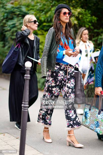 A guest wears sunglasses a black studded hat a black leather jacket a blue top with red floral prints fringed black pants with pink and white floral...