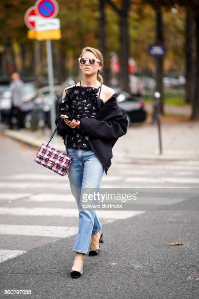 A guest wears sunglasses a black top with white floral prints a black jacket a pink and grey tweed Chanel bag blue jeans grey and black shoes outside...
