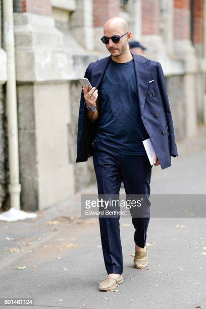 A guest wears sunglasses a blue blazer jacket a blue top blue pants camel shoes outside the Paul Smith show during Paris Fashion Week Menswear...