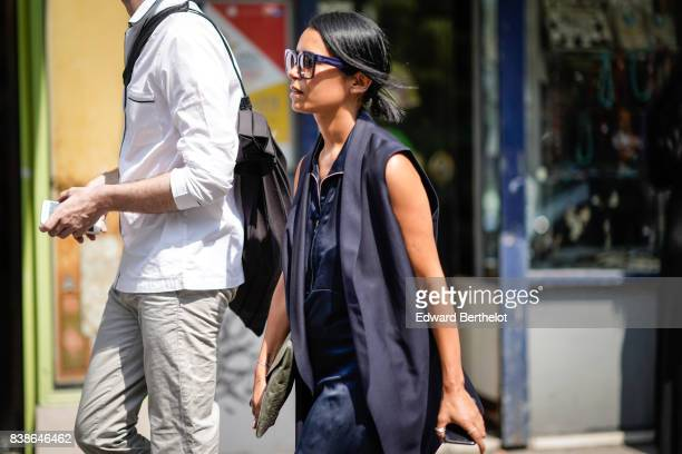 A guest wears sunglasses a blue sleeveless jacket a blue shirt outside the Y/Project show during Paris Fashion Week Menswear Spring/Summer 2018 on...