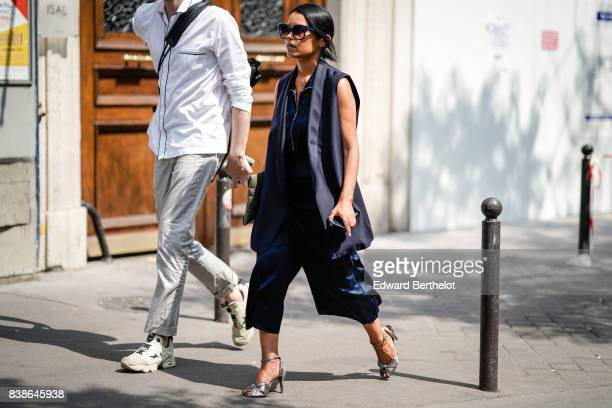 A guest wears sunglasses a blue sleeveless jacket large cropped pants silver heels outside the Y/Project show during Paris Fashion Week Menswear...