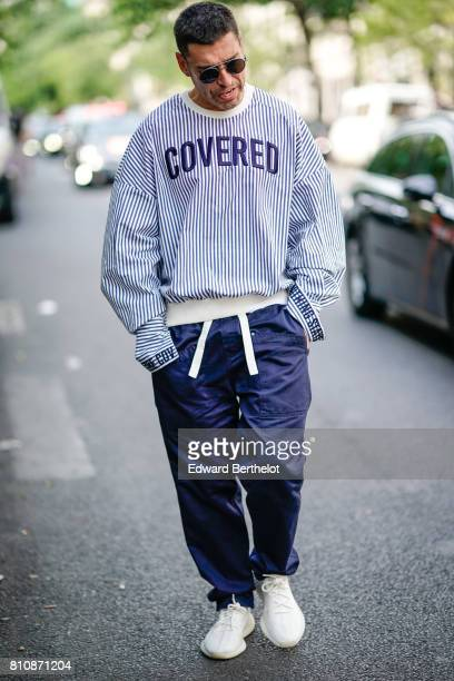 A guest wears sunglasses a blue striped 'covered' pull over blue pants white sneakers outside the Y/Project show during Paris Fashion Week Menswear...