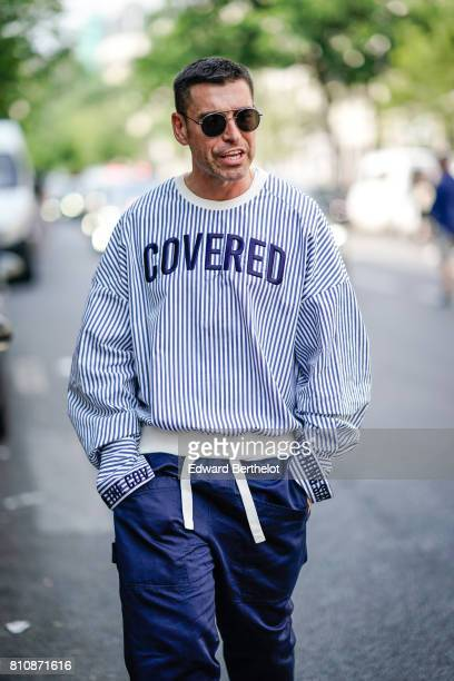 A guest wears sunglasses a blue striped pull over 'covered' a white belt blue pants outside the Y/Project show during Paris Fashion Week Menswear...