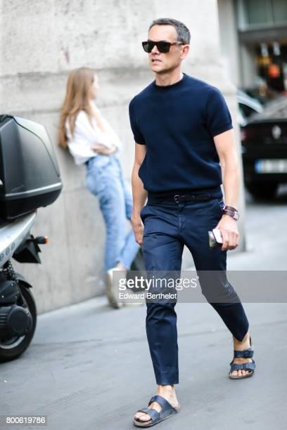 A guest wears sunglasses a blue top a belt blue denim jeans blue sandals outside the Hermes show during Paris Fashion Week Menswear Spring/Summer...