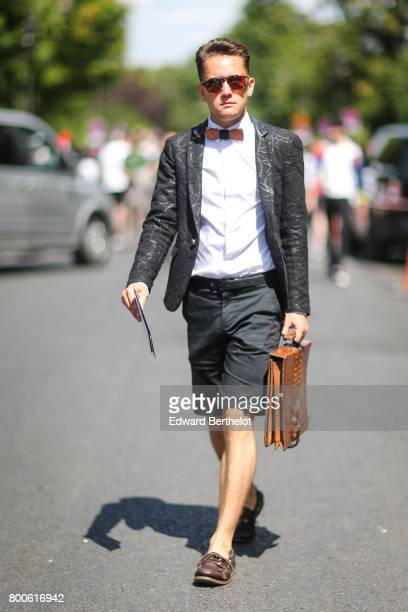 A guest wears sunglasses a bow tie a white shirt a silver blazer jacket a belt gray shorts a brown bag and brown shoes outside the Dior show during...