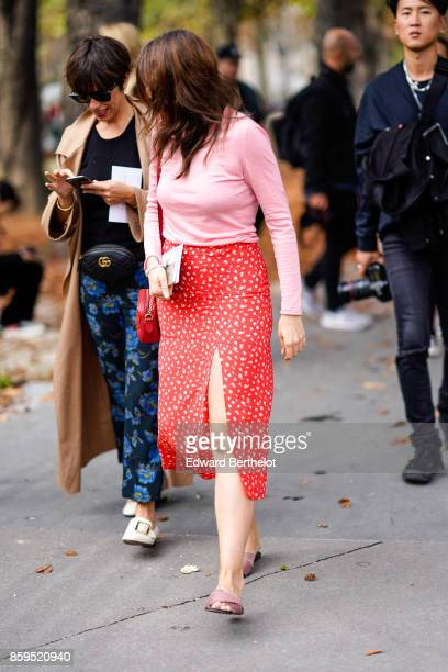 A guest wears sunglasses a camel trench coat a black top blue flower print pants beige slippers a black Gucci belt bag a guest wears a pink top a red...
