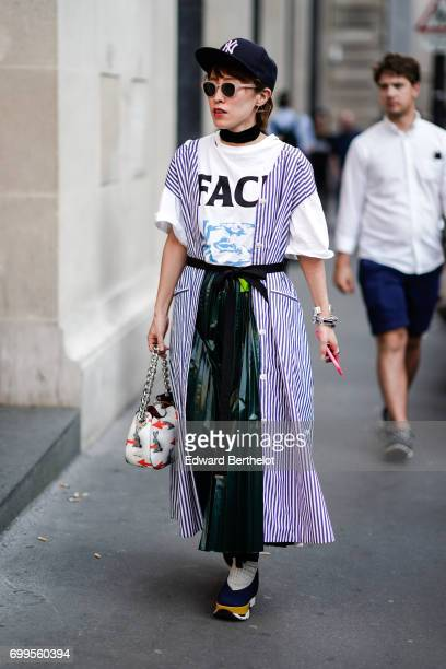 A guest wears sunglasses a cap a white oversized tshirt a striped sleeveless jacket a ruffled plastic dress and sneakers outside the OAMC show during...