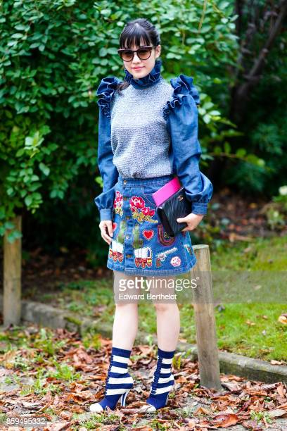 A guest wears sunglasses a flounced denim top a denim skirt with inserts of flower heart gun a black bag and blue and white striped boots outside...