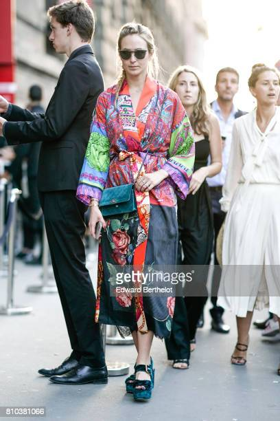 A guest wears sunglasses a flower print multicolor kimono dress green shoes a Chanel green bag outside the 'Christian Dior couturier du reve'...