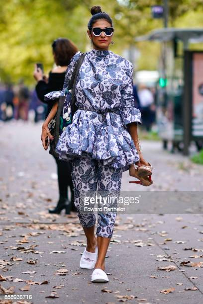 A guest wears sunglasses a flower print ruffle dress cropped pants white shoes outside CDG Comme des Garcons during Paris Fashion Week Womenswear...
