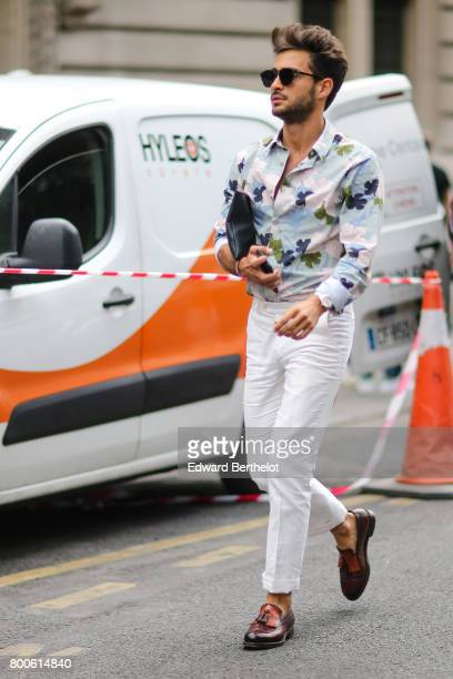 A guest wears sunglasses a flower print shirt white pants brown leather shoes outside the Dior show during Paris Fashion Week Menswear Spring/Summer...