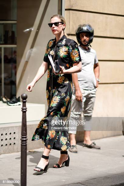 A guest wears sunglasses a flower print silk dress black heels shoes outside the Elie Saab show during Paris Fashion Week Haute Couture Fall/Winter...