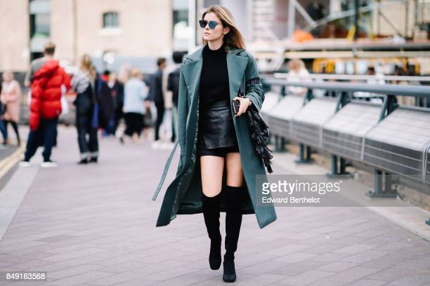 A guest wears sunglasses a green jacket a black top a black leather skirt black thigh high boots outside Versus during London Fashion Week September...