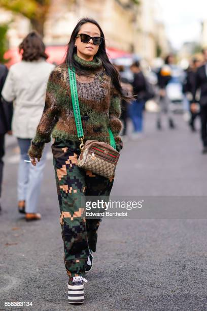 A guest wears sunglasses a military camo print turtleneck wool pull over a Gucci bag military camouflage print pants platform striped shoes outside...