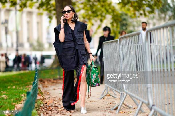 A guest wears sunglasses a navy blue oversize work vest black pants with red stripe a green bag with floral print white shoes outside Lanvin during...