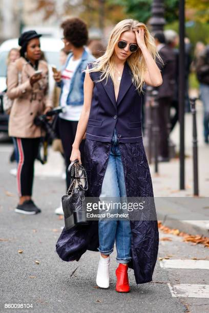 A guest wears sunglasses a navy blue sleeveless top a navy blue crushed fabric open skirt blue jeans a black bag red and white ankleboots outside...