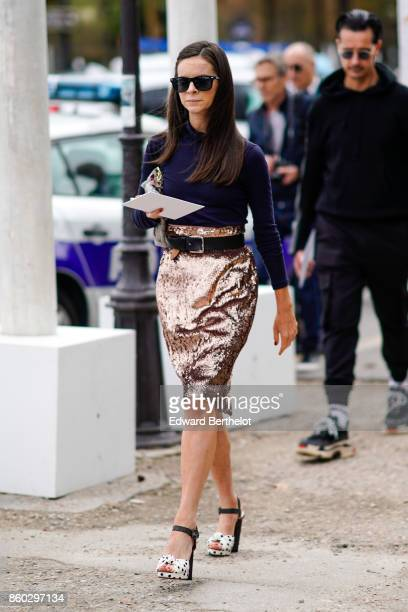 A guest wears sunglasses a navy blue turtleneck top a highwaisted pink lame skirt a large black belt black and white spotted platform shoes outside...