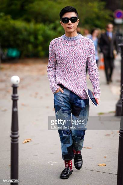 A guest wears sunglasses a pink and navy blue marled pullover denim shades of blue patchwork pants red print socks black shoes outside Lanvin during...